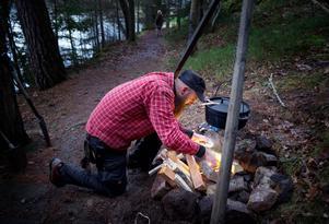 Johan Magnusson ordnar en eld där soppan ska kokas för att bli färdig tills deltagarna bastat färdigt.