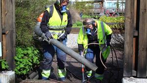 Proffsen i full gång. Päivi Bärgård, till höger, sprutar vatten på gruset för att oskadliggöra små partiklar som är farliga att andas in. Mia Andersson blåser grus och löv med en maskin. Mia och Päivi bär också masker för att skydda sig mot de partiklar som kan orsaka stenlunga.