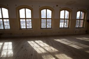 Längs huset långsida strömmar ljuset in genom de spröjsade fönstren.