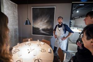 Johan Backéus berättar om konsten på väggarna. Här är en målning av lokala konstnären Åsa Näsman från Målsta.