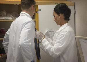 Anna och Hannes gör i ordning slipsen så att det ska se fint ut på den avlidne.