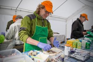 Joakim Glimsholt kryddar fisken och rullar in den i tunnbröd. Göran Glimsholt till höger i bild tar betalt av kunder.