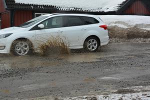 Ute på Alnövägen har stora hål bildats i vägen, som nu fyllts med vatten i takt med att snön smälter bort.