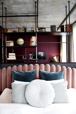 Fluffiga lakan, sammetskuddar och industridetaljer i en av Steam Hotels två sviter.