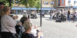 Publiken tittar och klappar med när sommarjobbare sjunger på Hökartorget.