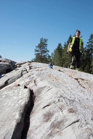 I Norvik fann arkeologerna 468 skålgropar inhuggna i berghällarna.  Arkeologen Kenneth Ihrestam tittar på groparna på bilden.