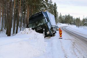 Lastbilen har av okänd anledning hamnat på sidan av vägen.