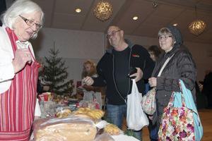 Elisabet Berntsson är en av husmödrarna som bakat vörtbröd och kaffebröd, Torbjörn och Solveig Larsson två av de många kunderna.