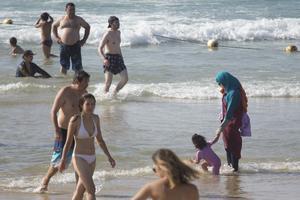 Kvinna i burkini i strandkanten. Foto: Ariel Schalit/AP Photo