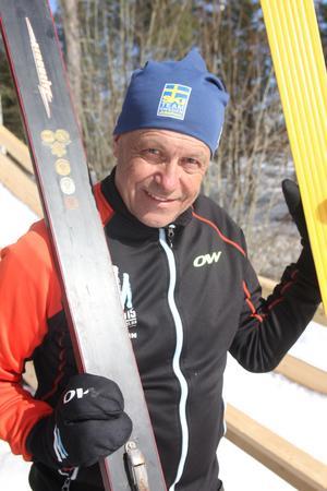 Börje håller upp skidorna han använde förr i tiden. De är mycket tyngre än moderna skidor.