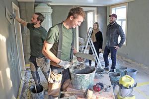 Flera hantverkare har varit med och hjälpt Mia och Gustav att förverkliga deras husdröm. Här jobbar Johan Härder och Johannes Larsson med lerklining på väggarna. Bakom i bild skymtas en kakelugn som fått följa med i flytten.