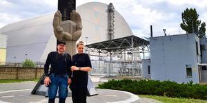 """Thomas Nordström och Lena Näsvall vid minnesmonumentet i Tjernobyl. Bakom dem finns olycksreaktorn under den rostfria byggnaden. """"Den är beräknad att hålla i 100 år"""", berättar Thomas."""