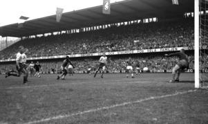 VM-final i fotboll mellan Sverige och Brasilien på Råsunda i Solna. Pelé har kommit fri och gör 3-1 till Brasilien. Varken Sven Axbom (längst till vänster), Sigge Parling eller Orvar Bergmark (till höger om Pelé) kan hindra Brasiliens 17-årige stjärna. Kalle Svensson i målet slänger sig förgäves. Matchen slutade 5-2 till Brasilien. Foto: Scanpix