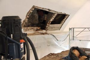 Två rejäla hål vid takfoten. Där kan man se att en stock murknat bort av möglet.