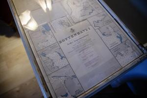 Under glasskivan har hon lagt gamla sjökort från kommunen.