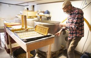Inne i sin lilla verkstad gör John Bergström sin Trogsta honung. Först ska den slungas och silas innan den kan hällas upp i burkar.