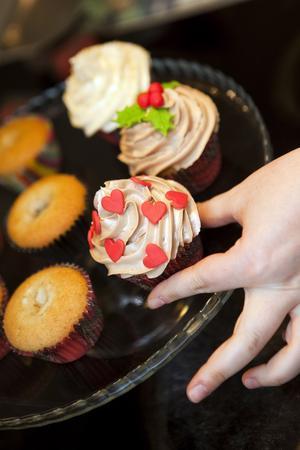 Varianter. Tania dekorerar kardemummakakor med gräddfluff i två smaker och färgad sockermassa. En variant är fylld med färskost, den andra med en bit choklad. Foto: Anders Forngren
