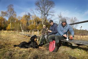 Fikapaus. Yvonne Larsson, Lars Hansén och Gert Straschewski från Roslagens ornitologiska förening, tar en paus i röjningsarbetet  i Riddersholm naturreservat. Hunden Bilbo har också hjälpt till att bära pinnar och förväntar sig en belöning.