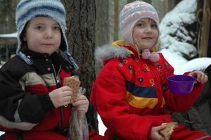 Fikade. Hanna Olenius, 5 år, och Kajsa Olenius, 8 år, från Ludvika fikar vid grillbrasan vid Tallmorkojan på Skedviskogen.