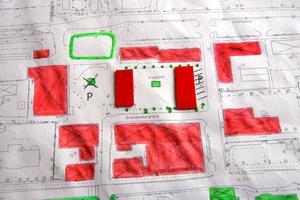 I mitten på skissen (med kraftigare rödfärg) har Karin Granér ritat in två hus på Postplans parkering för att rama in ett nytt, uppvärmt torg. Bilarna hänvisas till parkeringen vid kiosken och framför före detta Posthuset.