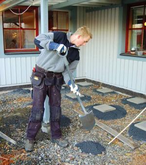 Stenplattorna vilar på sand. Peter Sellén ser till att det blir ungefär lika mycket sand i varje hög.