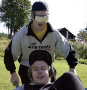 Det gäller att hålla tungan rätt i mun. Jonathan Dahlberg Larsson kör slalombanan med skottkärra utan att se och Rasmus Norin som har hörselskydd och därför inte hör, skriker ut vägen.