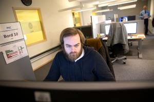 I de nya lokalerna på polishuset i Västerås arbetar Sebastian Darell som driftledare på PKC i Västmanland. I bakgrunden syns operatörer och gruppchefen Peter Jonsson.