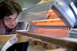 Värmelampa. Marielle Perup tar värme till hjälp för att mjuka upp det gamla kittet i innanfönstret och för att få en ren kittfals.