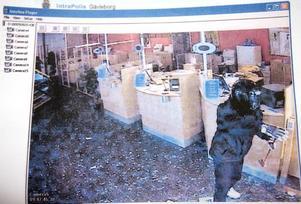RÅNAREN. Rånaren fångad i bankens kameror. Längst bort i lokalen ligger just nu fyra bankanställda gömda under samma skrivbord.