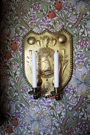 Ljusplåtarna med priskronor är från sekelskiftet 1800/1900. Tapeten Golden Lily av William Morris är parets favorit.