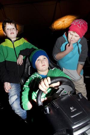 KÖRDE INNEBANDY OCH BILSPEL. Carl Thunhult, Samuel och Felix Norman från Årsunda hittade aktiviteter de gillade under Vinterfestens ungdomskväll. Här turas de om att köra rallyspelet Dirt 3.