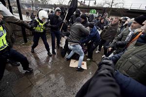Polis griper in under handgemäng mellan demonstranter och motdemonstranter i Stockholmsförorten Kärrtorp där oroligheter utbröt 2013.