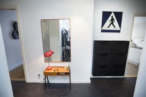 En retro hallmöbel i teak, mönster i spegeln, hallonröd lampa, Herr Gårman och svart skoskåp.