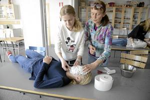 Lisa Östman lägger ansiktsmask på Clara Bernhult under överinseende av konstnären Karin Frostenson.