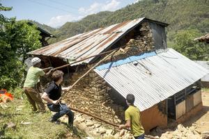 Med hjälp av bambupålar river byggteamet husen för att sedan kunna börja bygga nya. Foto: Jonas Gratzer