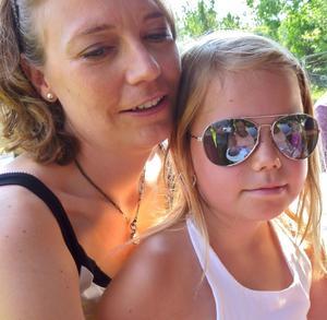 När jag tog bilden såg jag bara mamman och dottern i knäet, men när bilden kom upp i datorn fångades blicken av flickans solglasögon. Där ser man flickans moster med en ny kusin i det ena glaset och flickans lillasyster i det andra.