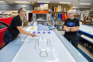 Mikael Nilsson diskuterar med  Mats Sköld hur en skylt till en kund ska utformas.