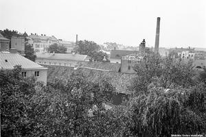 Här ser man en del av bryggeriets byggnader  bakom lövverket  1938. Till vänster ser man byggnaden som inrymde både konserthus och stadsbibliotek. Fotograf: Erik Larsson. (Bildkälla: Örebro stadsarkiv)