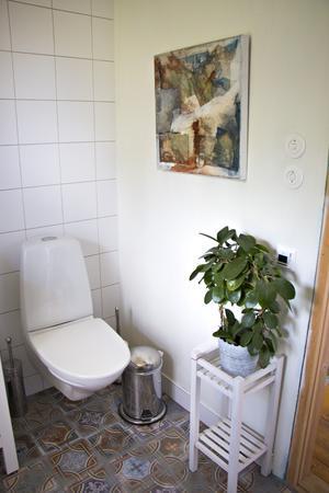 I en klädkammare på övervåningen har ett modernt badrum inretts. Med plats för både dusch, tvättmaskin och tumlare – och konst på väggarna. Blompidestalen fungerar även som toalettpappershållare.