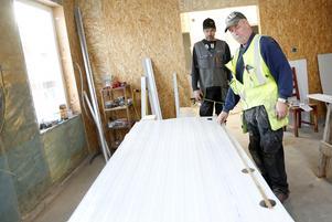 Per Östberg och Lars-Gunnar Lindström sätter upp väggplåtar i de blivande mejerilokalerna.