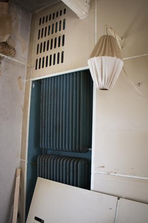 Den blå färgen från delar av fasaden och hallen återkommer även på insidan av skåp och som här på radiatorerna i vardagsrummet, De har nogsamt målats trots att de normalt göms bakom elementskydden och färgen bara kan anas genom öppningarna. Lampan på väggen är även den designad av Erskine.