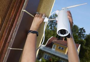 Monterar övervakningskamera på husknuten. Foto: Fredrik Persson/TT