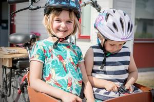 Ellie, 6 år, och Edith, 4 år, trivs med att sitta i lådcykeln. Och egna cyklar tar de sig fram på i full fart också.