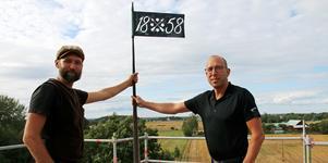 Nu är Kånsta kvarn renoverad till toppen. Martin Nilsson och Magnus Andersson håller i flaggan som visar året 1858 då kvarnen byggdes.