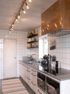 Kopparkåpan och lampan ger ett varmt sken i köket.