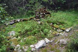 En gammal grund efter en fäbodstuga, där det funnits en eldstad med skorsten.