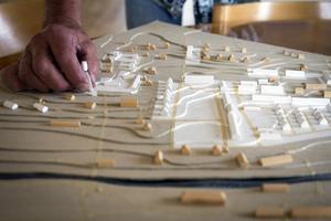 Hela halva Hammarby är Erskine. Allt som är vitt på modellen har han ritat. Handen som håller i det lossnade vattentornet tillhör Hammarbyprofilen Mats Mattsson, som sitter i kommunfullmäktige och också vill jobba för att bättre ta vara på kulturarvet efter Erskine.