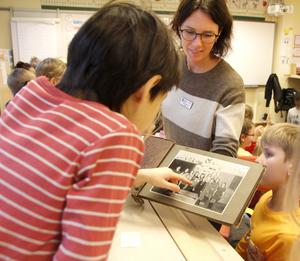 Läraren Emilie Svensson visar eleverna Kerstin Rodells gamla bilder från skolan.