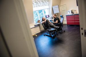 I rummet intill blir Christoffer Rossander tatuerad av Jens Arnkvist. Motivet? En ros och en leopard.