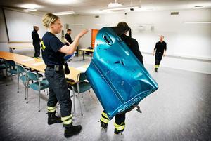 Brandmannen Johanna Rydberg och den bildörr som använts för att visa  vilket uselt skydd den är mot olika typer beskjutning.